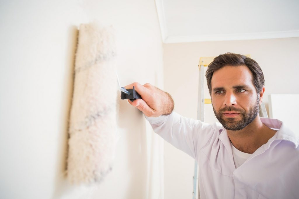 man rolling paint on the wall